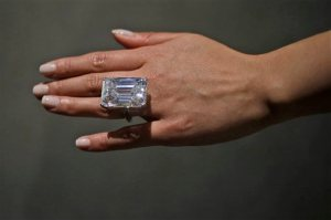 "A Sotheby's employee models a 100-carat emerald-cut diamond, Friday, April 17, 2015, in New York. The ""perfect"" 100-carat diamond in a classic emerald cut is going on the auction block, where it could fetch between $19 million to $25 million. Sotheby's will offer the white diamond on April 21, in New York.  (AP Photo/Mary Altaffer)"