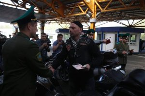 Belarus border guard shakes hands with a Russian biker as he checks his passport at Brest border check point on Belarus-Polish border on Monday, April 27, 2015. The bikers, including members of the Night Wolves group, set off from Moscow on Saturday with the aim of crossing into Poland before eventually reaching Berlin on 9 May. They are undertaking the journey despite Poland announcing it will refuse them entry into the country.  (AP Photo/Sergei Grits)
