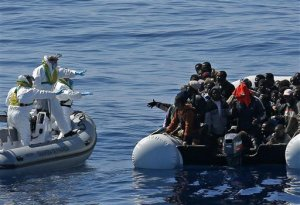 In this photo made available Thursday, April 23, 2015, an Italian Financial Police rescue unit approaches an inflatable dinghy crowded with migrants off the Libyan coast, in the Mediterranean Sea, Wednesday, April 22, 2015.  European Union leaders gathering for an extraordinary summit are facing calls from all sides to take emergency action to save lives in the Mediterranean, where hundreds of migrants are missing and feared drowned in recent days. (Alessandro Di Meo/ANSA via AP Photo) ITALY OUT