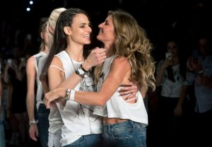 Brazilian supermodel Gisele Bundchen, right, and fellow Brazilian model Fernanda Tavares embrace at the end of the show from the Colcci Summer collection, at the Sao Paulo Fashion Week in Sao Paulo, Brazil, Wednesday, April 15, 2015. Bundchen, the Brazilian supermodel who has lit up catwalks around the world for 20 years, is retiring from the runway. (AP Photo/Andre Penner)