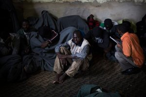FILE - In this file photo taken Friday, Nov. 29, 2013, African migrants cover themselves with blankets, after being captured by the Libyan Coast Guard while on a boat heading to Italy, in a detention center for illegal migrants in Abu Salim district on the outskirts of Tripoli, Libya. Libya's chaos has turned it into a large and lucrative funnel attracting migrants desperate to make the dangerous sea voyage to Europe. With no central authority to stop it, business is booming, creating a vicious circle that only translates into more tragedies in the Mediterranean. (AP Photo/Manu Brabo, File)