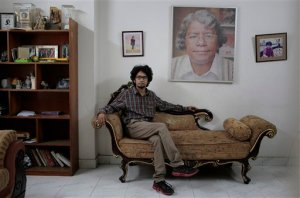 25-year-old Bangladeshi blogger Ananya Azad poses for a photograph at his house beside a portrait of his late father Humayun Azad, who was attacked a decade ago for his writings against Muslim extremism, in Dhaka, Bangladesh, Saturday, April 4, 2015. Ananya quit his job as a newspaper columnist and stopped writing blogs in recent months after receiving numerous threats for being critical of Islamic fundamentalism and politics driven by religion, but still posts critical comments on Facebook. Ananya says he's thinking about fleeing the country and spends much of his time indoors these days after a secularist blogger was hacked to death earlier this week in the streets of the capital, the second in less than a month. (AP Photo/ A.M. Ahad)