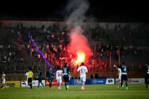 FILE - In this Sunday, Feb. 8, 2015 file photo, Ultras White Knights soccer fans light flares during a match between Egyptian Premier League clubs Zamalek and ENPPI at the Air Defense Stadium in a suburb east of Cairo, Egypt. At least 22 soccer fans were crushed to death outside an air defense stadium in Cairo after police fired tear gas to break up the crowd waiting in a fenced, narrow corridor to watch. Police accused the fans of attacking the force, and rioting to enter the stadium. On Tuesday, March, 17, 2015 the chief prosecutor general also referred 16 fans to trial, accusing them of belonging to the Muslim Brotherhood. (AP Photo/Ahmed Abd El-Gwad, El Shorouk Newspaper, File) EGYPT OUT