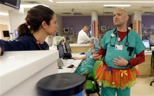 In this photo taken Tuesday, March 24, 2015, Dr. Bob Kaye, right, talks to registered nurse  Nicole Maggi on Tutu Tuesday at Joe DiMaggio Children's Hospital in Hollywood, Fla. (AP Photo/Alan Diaz)