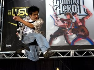 "FILE - In this July 7, 2007 file photo, Freddie Wong, 21, of Seattle, Wash.,  plays Guitar Hero II on stage at the World Series of Video Games, in Grapevine, Texas. After a five year absence, ""Guitar Hero"" and ""Rock Band"" are planning a reunion tour in 2015 on the current generation of video game consoles. While the new rendition of ""Guitar Hero"" is offering a revamped controller, ""Rock Band"" is promising backward compatibility.  (AP Photo/D.J. Peters, File)"