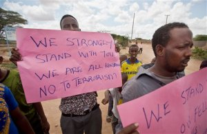 Kenyan Muslims demonstrate against Thursday's attack and in solidarity with non-Muslims who were targeted, on a street in Garissa, Kenya Friday, April 3, 2015. Al-Shabab gunmen rampaged through a university in northeastern Kenya at dawn Thursday, killing scores of people in the group's deadliest attack in the East African country. Four militants were slain by security forces to end the siege just after dusk. (AP Photo/Ben Curtis)