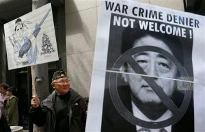 Peter Li, retired East Asian history professor from Rutgers University, left, holds up a sign next to a photo of Japanese Prime Minister Shinzo Abe as he and other Chinese American and Korean American protesters rally outside of the Japanese Consulate in San Francisco, Tuesday, April 28, 2015. Hundreds of people protested outside the Japanese Consulate Tuesday, calling on Prime Minister Shinzo Abe to apologize for his country's atrocities toward other Asian countries during World War II. The protest came as Abe met with President Barack Obama in Washington, D.C., ahead of the prime minister's three-day visit to California this week. (AP Photo/Jeff Chiu)
