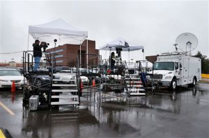 Television journalists work on platforms in the parking lot of the Arapahoe County Justice Center, on the first day of the trial of James Holmes, in Centennial, Colo., Monday, April 27, 2015. Holmes acknowledges killing 12 people and wounding 70 more inside a packed movie theater on July 20, 2012, but has pleaded not guilty by reason of insanity. (AP Photo/Brennan Linsley)