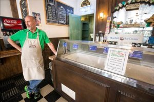 Charlie Pyle, owner of Must Be Heaven Ice Cream Parlor, stands by his ice cream case on Tuesday, April 21, 2015, in Brenham, Texas. In compliance with the Blue Bell Ice Cream recall, Pyle pulled all ice cream from his freezers. (Brett Coomer/Houston Chronicle via AP)