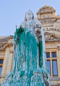 In this photo taken Friday, April, 10, 2015, a statue of Britain's Queen Victoria, outside the Port Elizabeth city library in South Africa, after being splashed with green paint. Excrement thrown at the statue of British colonialist Cecil John Rhodes began a wave of vandalizing protests in South Africa. Memorials to South Africa's colonial past were rejected as symbols of oppression by mainly young black protesters, as statues of British monarchs Queen Victoria and King George V were splashed with paint, in the cities of Port Elizabeth and Durban respectively.