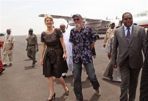 Released Dutch hostage Sjaak Rijke, second right, walks with an unidentified Dutch diplomat, center left,  as he arrives at the airport  in Bamako, Mali, Tuesday, April 7, 2015. French special forces on Monday freed Rijke who had been  held hostage since being kidnapped in 2011 by extremists in Mali, the government said. There was no word on the fate of the two men who were abducted at the same time.(AP Photo/Baba Ahmed)