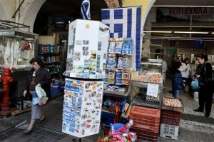 A Greek flag for sale is hanged on a wall as people make their shopping at the main meat market in the northern port city of Thessaloniki , Greece, on Friday, April 24, 2015. Greece's Finance Minister Yanis Varoufakis came under fire Friday from his peers in the 19-country eurozone for failing to come up with a comprehensive list of economic reforms that are needed if the country is to get vital loans to avoid going bankrupt.(AP Photo/Giannis Papanikos)