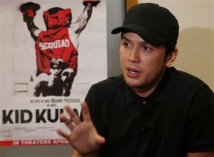"In this April 7, 2015 photo, Filipino filmmaker Paul Soriano gestures beside a poster of the movie ""Kid Kulafu,"" a movie about Filipino boxing hero Manny Pacquiao's childhood, during an interview in suburban Makati, south of Manila, Philippines. The movie depicts the impoverished world Pacquiao grew up in before he boxed his way to fame, fortune and power, becoming the world's only eight-division boxing champion, one of its highest-paid athletes and the wealthiest member of the Philippine House of Representatives. The movie will be shown in more than 100 theaters around the country starting Wednesday, April 15, 2015 ahead of Pacquiao's May 2 megafight with Floyd Mayweather. (AP Photo/Aaron Favila)"