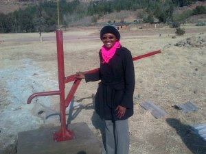 Jennifer Jiggetts stands by a water pump that's helping people in the town of Lesotho, South Africa.