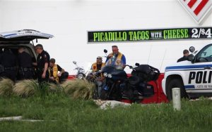 Police detain and watch members of various motorcycle clubs near a Twin Peaks restaurant in Waco, Texas, Sunday, May 17, 2015. A shootout among rival motorcycle gangs at the popular Texas restaurant left nine bikers dead and more than a dozen injured, a police spokesman said Sunday. (AP Photo/John L. Mone)