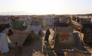 In this Thursday, May 21, 2015 photo, an Afghan refugee woman walks near her tent in a makeshift camp on the outskirts of Kunduz province, north of Kabul, Afghanistan. When the Taliban descended a month ago on Dam Shakh, a hamlet on the wheat-growing plains of northern Afghanistan's Kunduz province, nobody was prepared. By the time they were beaten back from the provincial capital of Kunduz, more than 100,000 people were forced from their homes and total of 204 war-wounded were admitted to Kunduz's only trauma hospital, run by French NGO Medecins Sans Frontieres in less than a month. (AP Photo/Rahmat Gul)