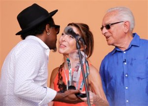 Cuban sculptor Alexandre Arrechea, left, gets his U.S.-based Farber Foundation award from the hands of Howard Farber, right, and his wife Patricia in Havana, Cuba, Wednesday, May 20, 2015.  Arrechea was named Cuban Artist of the Year by the foundation at a ceremony in Old Havana. The award comes with a $10.000 prize. (AP Photo/Desmond Boylan)