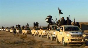 "FILE - In this undated file photo released by a militant website, which has been verified and is consistent with other AP reporting, militants of the Islamic State group hold up their weapons and wave its flags on their vehicles in a convoy on a road leading to Iraq, while riding in Raqqa city in Syria. The notion that young women are traveling to Syria solely to become ""jihadi brides"" is simplistic and hinders efforts to prevent other girls from being radicalized, new research suggests. Young women are joining the so-called Islamic State group for many reasons, including anger over the perceived persecution of Muslims and the wish to belong to a sisterhood with similar beliefs, according to a report released Thursday, May 28, 2015, by the Institute for Strategic Dialogue and the International Center for the Study of Radicalization at King's College London. (Militant website via AP, file)"
