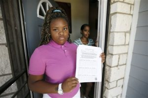 Natod'Ja Washington, front, 16, poses for a photo with her mother Natasha Holloway at their home as Washington holds a student sign in sheet for truancy court Friday, June 19, 2015, in Dallas. The form must be signed by all of her teachers confirming Washington's attendance in school. (AP Photo/Tony Gutierrez)