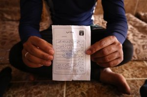 """In this Wednesday, May 27, 2015 photo, Salim Ahmed, a former Iraqi Army member, holds the """"repentance card"""" he received from the Islamic State group in June 2014 shortly after the militants took over his home village of Eski Mosul in northern Iraq. The document is part of the apparatus of control the Islamic State group has constructed across its self-declared """"caliphate,"""" the territory it conquered in Syria and Iraq. (AP Photo/Bram Janssen)"""