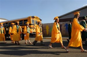 ADVANCE FOR SATURDAY, MAY 30, 2015 AND THEREAFTER - In this May 22, 2015 photo, graduating seniors head towards the football stadium prior to the start of their graduation ceremony in  Louisa, Va. The class of 2015 spent nearly their entire high school career attending classes in modular trailers after the school was irreparably damaged in the 2011 earthquake. (Dave Ellis/The Free Lance-Star via AP)