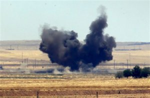 In this photo taken from the Turkish side of the border between Turkey and Syria, in Akcakale, Sanliurfa province, southeastern Turkey, smoke from a US-led airstrike rises over the outskirts of Tal Abyad, Syria, Sunday, June 14, 2015. Syrian Kurdish fighters closed in on the outskirts of a strategic Islamic State-held town on the Turkish border Sunday, Kurdish officials and an activist group said, potentially cutting off a key supply line for the extremists' nearby de facto capital. Taking Tal Abyad, some 80 kilometers (50 miles) from the Islamic State stronghold of Raqqa, would mean the group wouldn't have a direct route to bring in new foreign militants or supplies.(AP Photo/Lefteris Pitarakis)