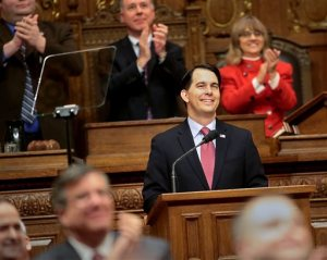 FILE - In this Feb . 3, 2015 photo, Gov. Scott Walker acknowledges applause from members of the Wisconsin State Legislature before delivering his state budget address at the state Capitol in Madison, Wis. Walker proposed, and a Republican-controlled committee later approved, eliminating tenure in state law as part of a larger overhaul of higher education policy that he is talking about to Republican voters around the country. (John Hart/Wisconsin State Journal via AP, File)