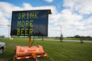 """An electronic road sign with the words """"DRINK MORE BEER"""" is shown on Tuesday, June 23, 2015, in Frankenlust Township, Mich. An auction company has sold the sign for about $600 after it attracted attention from passers-by with its message.  (Yfat Yossifor/The Bay City Times via AP) LOCAL TELEVISION OUT; LOCAL INTERNET"""