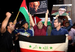 Supporters of Tariq Aziz, the only Christian in Saddam Hussein's inner circle, hold the Iraqi flag and portraits of him outside the Arab Medical Center, where his body was brought from Iraq, in Amman, Jordan, early Saturday, June 13, 2015. Aziz died June 5 at age 79. He had been in prison in Iraq since the U.S.-led invasion of Iraq in 2003 and suffered a series of strokes. He faced execution for his role in a government that killed hundreds of thousands of Iraqis. Jordan's government agreed to a request by Aziz's family to bury him in Jordan. (AP Photo/Khaled  Al Odat)