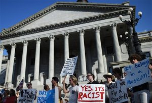 Protesters stand on the South Carolina Statehouse steps during a rally to take down the Confederate flag, Saturday, June 20, 2015, in Columbia, S.C. Rep. Doug Brannon, R-Landrum, said it's past time for the Confederate flag to be removed from South Carolina's Statehouse grounds after nine people were killed at the Emanuel A.M.E. Church shooting. (AP Photo/Rainier Ehrhardt)