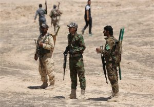 Fighters from the Badr Brigades Shiite militia patrol at the front line, in Kessarrat, located (70 kilometers)  north west of Baghdad, Iraq,  Friday, June 12, 2015. Despite concerns over heightened sectarian strife, Shiite militiamen continue to pour into Iraq's Anbar province with the hope of recapturing the city of Fallujah from the Islamic State group. As the U.S. prepares to send an additional 450 trainers to Iraq, the Iranian-backed militias say that coalition assistance only hurts their efforts, contradicting statements by the Iraqi government that more international support is needed. (AP Photo/Hadi Mizban)