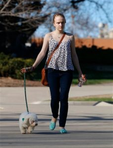 In this April 2015 photo, sexual assault victim Emily Kollaritsch is shown with her service dog, Candy, in East Lansing, Mich. If it weren't for Candy, Kollaritsch, who suffers from post-traumatic stress disorder, says she would not have been able to return to school. A growing backlog at the U.S. Department of Education has some sexual assault victims waiting years to have their cases resolved. (AP Photo/Al Goldis)