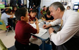 FILE - In this May 14, 2015, file photo, Education Secretary Arne Duncan visits with young student Mario Corona, age 6, in kindergarten at McGlone Elementary School in the Montbello section of Denver. The Obama administration is giving seven more states and the District of Columbia more flexibility from the requirements of the Bush-era No Child Left Behind education law. In addition to Washington, Duncan on June 23 renewed waivers for Georgia, Hawaii, Kansas, Missouri, Nevada, New York, and West Virginia. (AP Photo/Brennan Linsley, File)