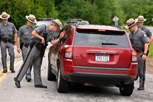 New York State Trooper Steven J. Gill searches a vehicle in Malone, N.Y., Tuesday, June 23, 2015, while searching for two prison escapees from Clinton Correctional Facility. Police began focusing intensely on an area 20 miles west of the prison that inmates David Sweat and Richard Matt escaped from prison on June 6. (Jason Hunter/The Watertown Daily Times via AP)  SYRACUSE OUT