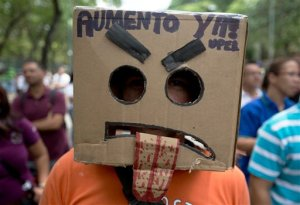 """In this Thursday, May 28, 2015 photo, a teacher with the head covered by a box with a sign that  reads in Spanish """"Salary raise now"""" during a protest at Venezuela's Central University, UCV, in Caracas, Venezuela. More than 700 of the 4,000 professors who once taught at the highly respected Central University have quit during the last four years, some taking better-paying jobs in other fields inside the country while others have been lured to more attractive academic posts at universities abroad. (AP Photo/Fernando Llano)"""