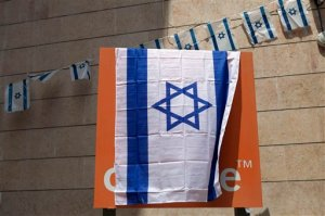 """The Orange company logo is seen covered with an Israeli flag at the """"Partner Orange"""" Communications Company's offices in the city of  Rosh Haain, Israel, Thursday, June 4, 2015. An Israeli Cabinet minister has called on the French president to fire the chief executive of French telecom giant Orange. Culture Minister Miri Regev issued her appeal on Thursday, a day after Orange's CEO announced in Cairo that he would like to sever his company's ties to Israel as soon as possible. (AP Photo/Dan Balilty)"""