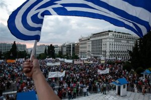 An anti-austerity protester waves a Greek flag during a rally in front of the parliament in Athens, Greece, on Sunday, June 21, 2015. A day ahead of a crucial emergency eurozone summit, European leaders renewed efforts to reach a deal between Greece and its creditors that would allow the debt-ridden country to avoid a default and a potentially disastrous exit from the euro. (AP Photo/Yorgos Karahalis)