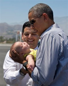 President Barack Obama holds one of the twin daughters of Rep. Raul Ruiz, D-Calif., background, as he arrives on Air Force One at Palm Springs International airport in Palm Springs, Calif, Saturday, June 20, 2015. The president will be golfing in the area this weekend. (AP Photo/Carolyn Kaster)