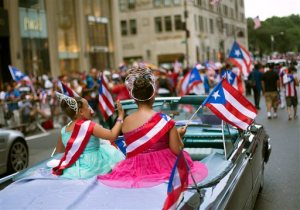 Kaylee Vazquez, 8, left, and Jayda Vazquez, 12, ride atop a convertible as the annual Puerto Rican Day Parade makes its way up New York's Fifth Avenue, Sunday, June 14, 2015. Hundreds of thousands of people turned out for the parade led by the island's governor. (AP Photo/Kevin Hagen)