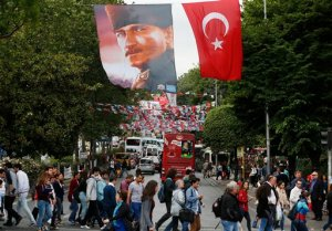 FILE - In this Thursday, May 28, 2015 file photo, a portrait of Turkish Republic founder Mustafa Kemal Ataturk, top left, and a Turkish flag, right, backdropped by Turkish parties' banners and flags fly over a street in Istanbul, Turkey. Following the June 7, 2015 elections, experts agree on one thing: No one really knows what's going to happen next. Turkey's election left Turkey's long-ruling Justice and Development Party _ known by its Turkish acronym, AKP _ short of the majority it needs to govern alone, meaning it will have to turn to one (or more) of the three opposition parties to secure its hold on government. (AP Photo/Lefteris Pitarakis, File)