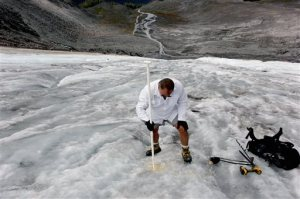In this Aug. 7, 2015, photo Oliver Grah, a scientist for the Nooksack Indian Tribe, measures ice melt on the Sholes Glacier in Mount Baker, Wash. Glaciers on Mount Baker and other mountains in the North Cascades are thinning and retreating. (AP Photo/Manuel Valdes)