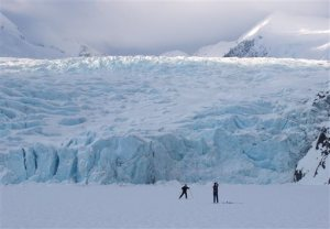In this March 29, 2006 photo, a skier poses for a photograph on Portage Lake in front of Portage Glacier, about 50 miles south of Anchorage, Alaska. The Portage Glacier, which is a major Alaska tourist destination near Anchorage has retreated so far it no longer can be seen from a multimillion-dollar visitors center built in 1986.  President Obama leaves Monday, Aug. 31, 2015 for a three-day visit to the 49th state in which he will speak at a State Department climate change conference and become the first president to visit the Alaska Arctic. There and even in the sub-Arctic part of the state, he will see the damage caused by warming, damage that has been evident to scientists for years. (Evan R. Steinhauser/Anchorage Dispatch News via AP, File)