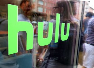 """This Saturday, June 27, 2015 photo shows the Hulu logo on a window at the Milk Studios space in New York, where a replica of the """"Seinfeld"""" set was on display, in New York. The cable network Epix jumped from Netflix to Hulu, the companies announced late Sunday, Aug. 30, 2015, landing a multiyear, digital subscription video on demand deal with the streaming service. (AP Photo/Dan Goodman)"""