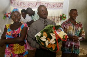 In this photo taken Sunday, Aug. 16, 2015, Ebola survivor Victoria Yillia, left, Pastor Gabriel Abu, center, holding Yillia's newborn son Barnabas and Anthony Yillia, right, sing before prayers during a church service in Kenema, on the outskirts of Freetown, Sierra Leone. Ebola did not take Victoria Yillia's life, and it could not prevent the birth of her son. They called the child Barnabas - a Biblical name that often translates as the son of encouragement or consolation. (AP Photo/Sunday Alamba)