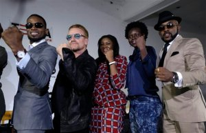 """Irish rock star Bono, second left, poses with African music stars after a press conference in Lagos, Nigeria, Friday, Aug. 28, 2015, African stars and rock star Bono say music can help push for the empowerment of women globally. Bono and the top African male musicians D'banj, Diamond and Banky W announced Friday that they will be included in a remix of the song """"Strong Girl"""" - a rallying cry for women's empowerment which features top African female talent. (AP Photo/Sunday Alamba)"""