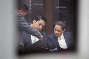 Guatemala's former Vice President Roxana Baldetti, right, talks with her lawyer Mario Cano as she waits for her hearing inside a courtroom, photographed through a window in Guatemala City, Monday, Aug. 24, 2015. Baldetti was detained Friday in connection with a customs corruption scandal that previously led to her resignation. Prosecutors are also seeking to investigate President Otto Perez Molina. (AP Photo/Moises Castillo)