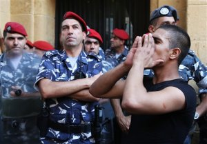 A Lebanese anti-government protester stands in front of policemen, as he shouts slogans outside the Environment Ministry in support of activists staging a sit-in inside, in downtown Beirut, Lebanon, Tuesday, Sept. 1, 2015. Lebanese security forces dragged a number of activists out of the Environment Ministry in downtown Beirut, where they were staging an hours-long sit-in on Tuesday demanding the minister's resignation over a trash crisis that has ignited mass protests. (AP Photo/Bilal Hussein)