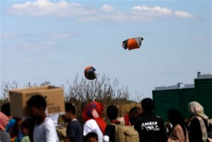 Migrant tents are caught in the wind and fly into the air over makeshift migrant camp in Roszke, southern Hungary, Wednesday, Sept. 9, 2015. Leaders of the United Nations refugee agency warned Tuesday that Hungary faces a bigger wave of migrants in the next few days and will need international help to provide aid and shelter on its border.(AP Photo/Darko Vojinovic)