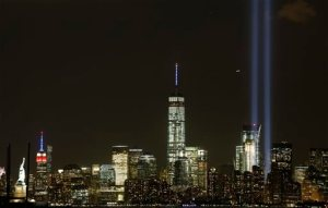 The Tribute in Light rises above the New York skyline, including the Statue of Liberty, left, the Empire State Building, second left, and One World Trade Center, center, Friday, Sept. 11, 2015 in a view from Bayonne, N.J. It was the 14th anniversary of the Sept. 11 terror attacks on Friday. (AP Photo/Mark Lennihan)