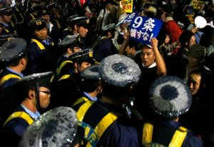 In this Friday, Sept. 18, 2015 file photo, a protester shouts slogans as he is surrounded by police officers during a rally against the Japanese government in front of the parliament building in Tokyo. Japan's parliament is moving toward final approval of legislation that would loosen post-World War II constraints placed on its military, an issue that has sparked sizeable street protests and raised fundamental questions about whether the nation needs to shift away from its pacifist ways to face growing security challenges. (AP Photo/Shuji Kajiyama, File)